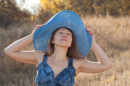 Beautiful woman in big blue hat on nature, looking up photo
