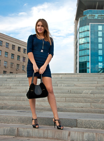 Young beautiful blond woman in dark blue dress near office building photo
