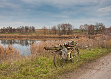 the old rusty bicycle near lake in Autumn photo