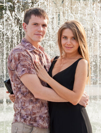 Happy young love couple standing near fountain photo