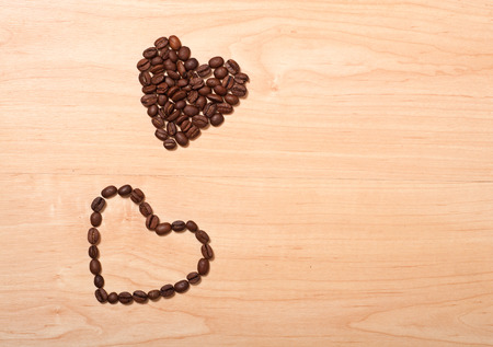 cofe: two coffee beans hearts on wooden background, love concept