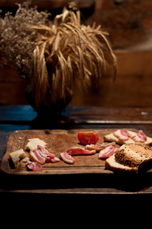 leavings: Bacon, tomato and bread on wooden board Stock Photo