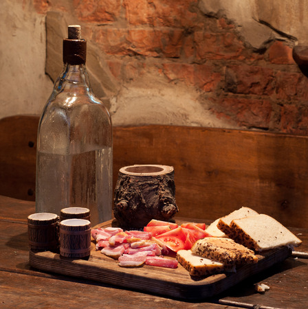 drunkenness: Ukrainian Moonshine and bacon, tomato and bread on table