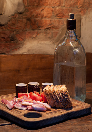 drunkenness: Russian Vodka and bacon, tomato and bread on wooden table