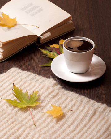 Cup of coffee, open book, autumn leaves ans wool scarf on table Imagens