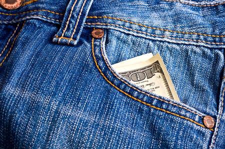 signo de pesos: Dólares en el bolsillo de los pantalones vaqueros azules