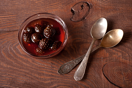 confiture: The Confiture from fir cones and two spoons on wooden table