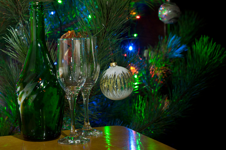 lighted: Two glasses and bottle of champagne in front of lighted christmas tree