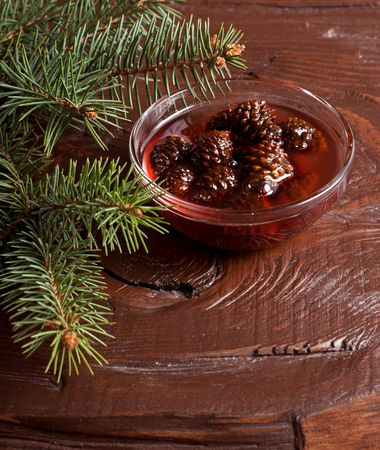 fir cones: The Confiture from fir cones in dish on wooden table