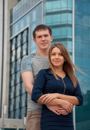 Happy young love couple standing in street of big city photo