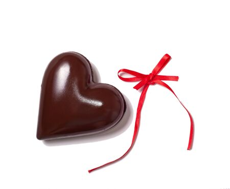 big chocolate heart and red ribbon on white background