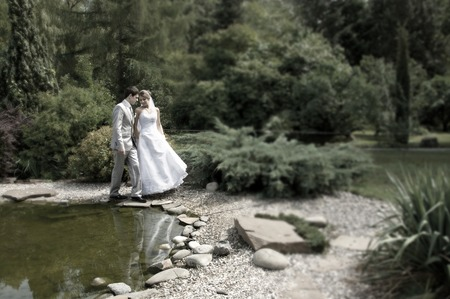 Bride and groom walking near lake in the beautiful park photo