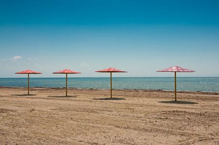 uninhabited: Black sea coast. Four parasols on the empty sandy beach.
