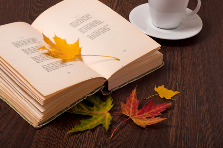 Cup of coffee, book and autumn leaves on wooden table. Autumn concept.