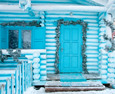 Decorating facade of wooden house for the Christmas Holidays
