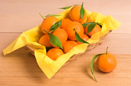 Tangerines with green leaves in a basket on wooden table Banque d'images