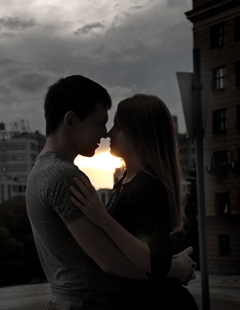 Happy young couple standing in street of city and enjoying sunset. Love couple on background of sunset. Love concept