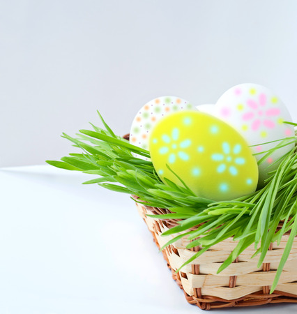 Painted Easter eggs on green grass in basket on white background