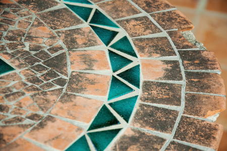A mosaic element on an old table, orange and blue.