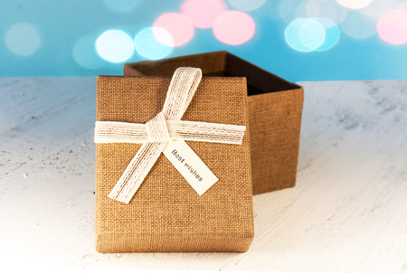 A brown gift box and a beige ribbon with a tag on a light background. A Christmas gift.Toning and blur