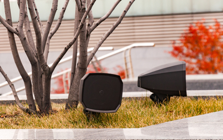 Modern loudspeakers installed in the park near the stairs, strewn with autumn leaves