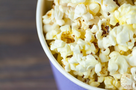 Popcorn in a bucket bucket is a top view on a dark wooden background. Macro shot from above Stock Photo