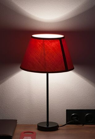 Intimate atmosphere in the hotel room. Bedside table on which lie the leather folder of the menu, do not disturb the sign and the lamp with a textile lampshade. Vertical shot