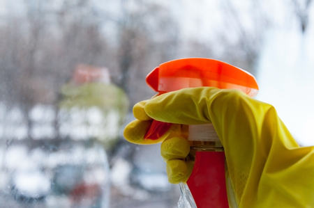 A hand in a rubber glove spray means for washing windows on the glass