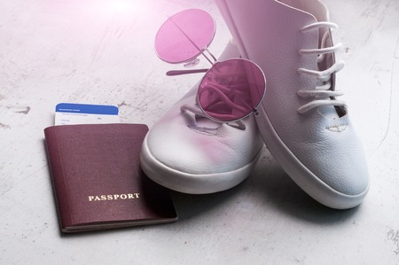 Russian passport with a boarding pass for the plane, white sports shoes and pink sunglasses. Travel concept Selective focus