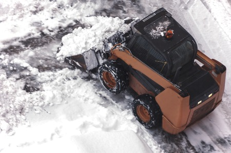 A small urban snow removal machine works in the courtyard of a residential building. View from above. Selective focus Stock Photo