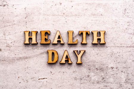 Inscription HEALTH DAY in wooden letters on a light background.