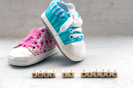 Pink and blue baby booties on a light background. Inscription does it matter Banco de Imagens