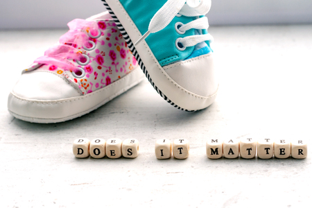Pink and blue baby booties on a light background. Inscription does it matter Stock Photo