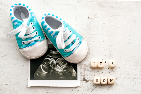 Blue baby booties with a picture of ultrasound for 20 weeks on a light background. Inscription its son