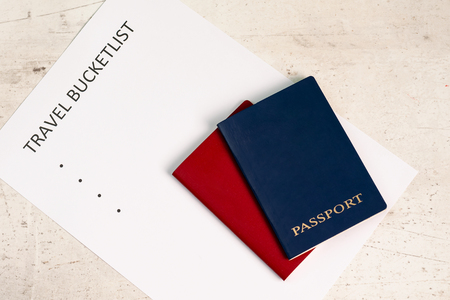 Blue and red travel passports on a light background, next to the inscription travel bucketlist