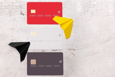 Three bank cards on a light background. Near paper planes. The concept of movement and waste of money