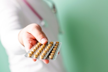 The doctor holds out the pills in his hand. Medical care concept. Selective focus