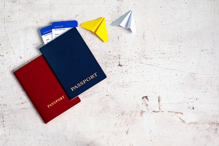 Two travelers passports red and blue with boarding passes for the plane. Near paper planes. Travel concept