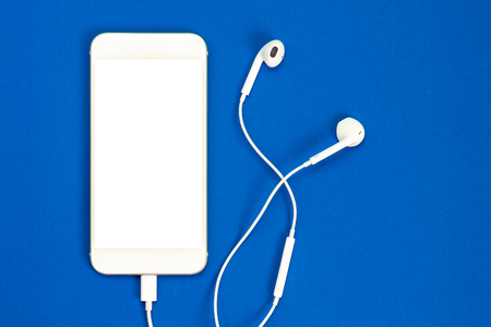 White smartphone on the blue background with headphones. View from above