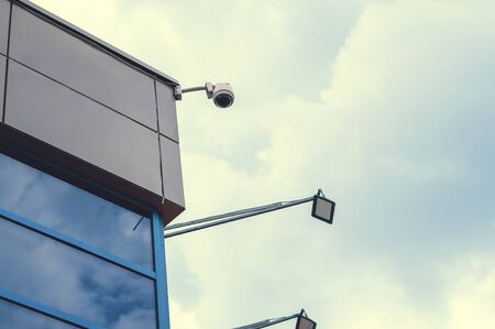 Surveillance camera on the corner of the house. Security and control.