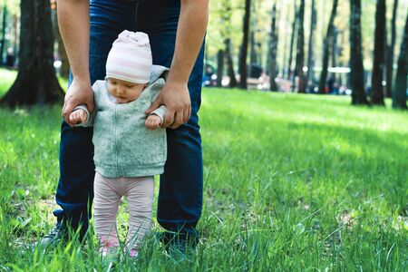 A child learns to walk with dad on the grass in the park. Spring walk. Paternity