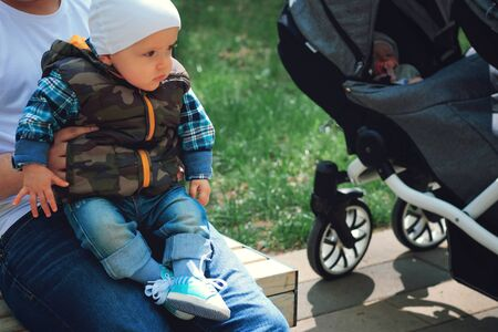 A child in the arms of his dad on the street, spring. Father walks with the child. Stroller for twins.
