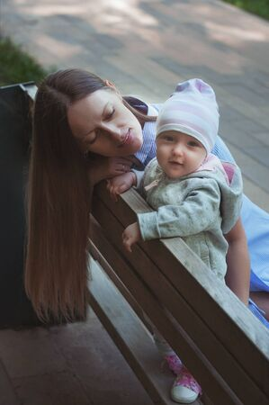Baby with mom on the bench in the park. Mom walks with a child