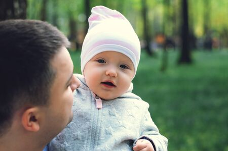 One year old girl in the arms of her father on the street, spring. Father walks with the child. First steps of the daughter Reklamní fotografie