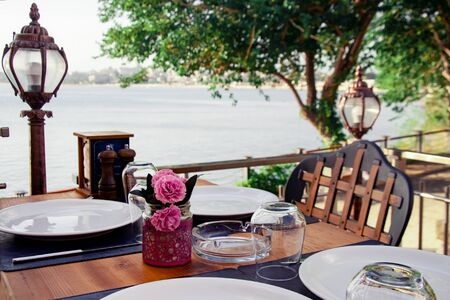 Served table in a summer cafe. The sea in the background. Wooden furniture, white flowers