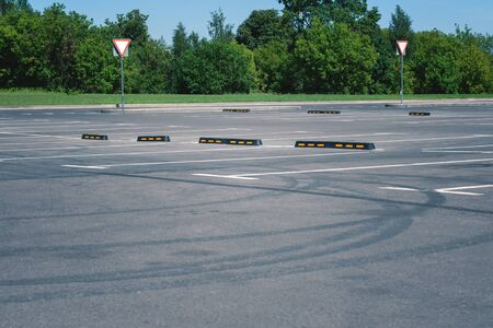 Modern rubber barrier for cars in the summer parking. Tire tracks on asphalt