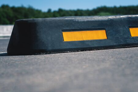 Modern rubber barrier for cars in summer parking. Close-up