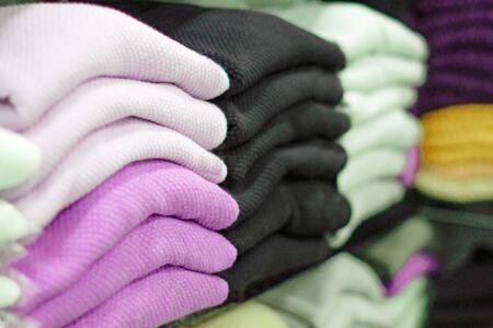 Ropa abrigada cuidadosamente doblada en el estante de una tienda. Sudaderas, suéteres, jerséis, cárdigans, sudaderas con capucha, bobmers con montones en el estante. Almacenamiento de ropa. Rango de tamaño