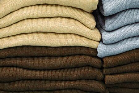 Ropa abrigada cuidadosamente doblada en el estante de una tienda. Sudaderas, suéteres, jerséis, cárdigans, sudaderas con capucha, bobmers con montones en el estante. Almacenamiento de ropa. Rango de tamaño Foto de archivo