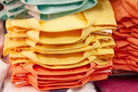 Bright colored shirts are stacked in a shop window. Size range, convenience of purchase